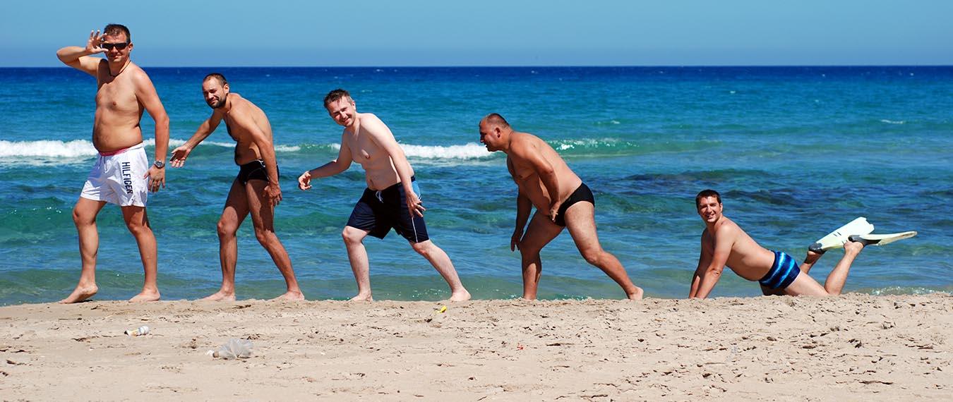 Męska część załogi rejsu ustawiona na plaży w Tunezji ustawieni jak na obrazach przedstawiających ewoluję homo sapiens