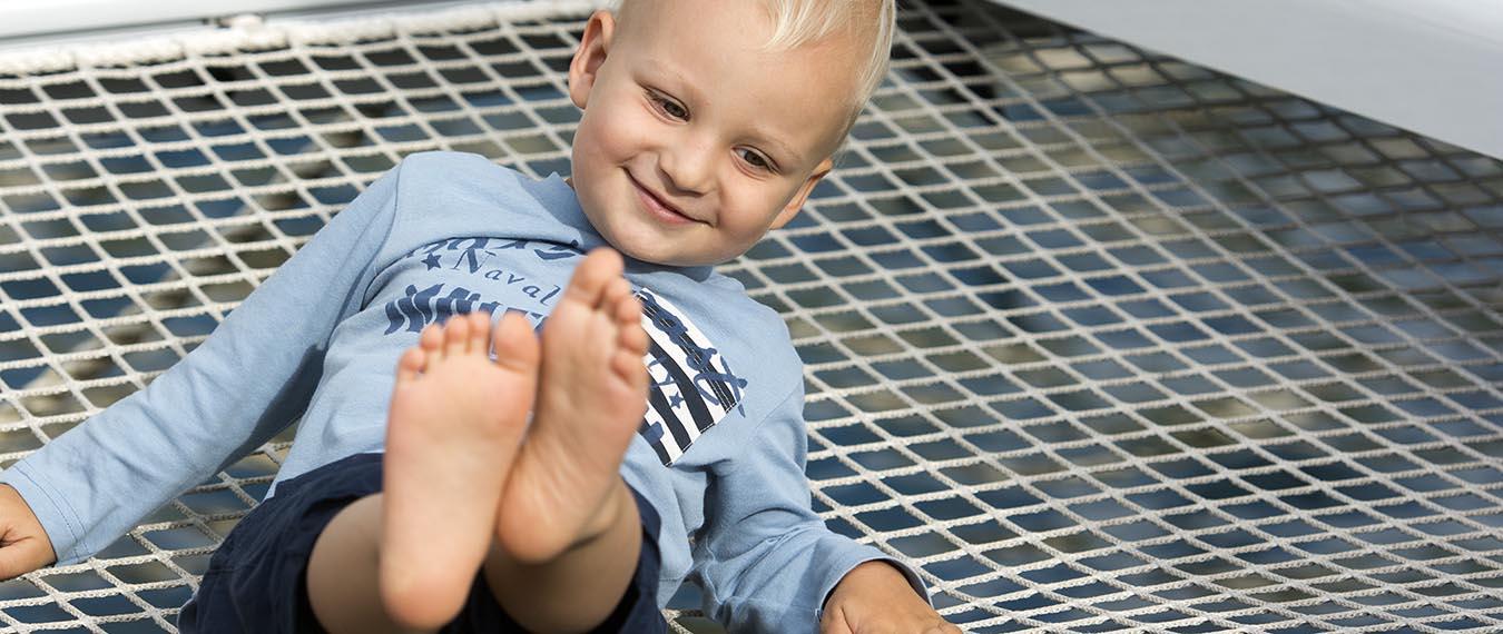 dziecko na siatce katamaranu podczas rejsu we Włoszech