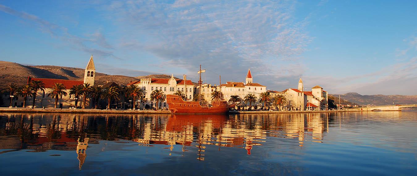 Zachód słońca nad starówką w Trogirze w Chorwacji. Widoczne odbicia statku i budynków w wodach zatoki